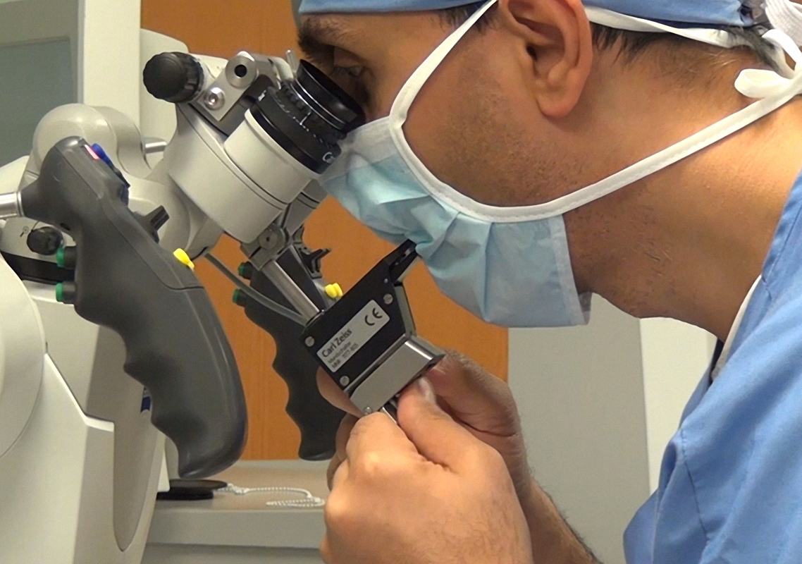 Figure 2: The mouthswitch is adjusted before I begin the operation and the microscope is draped.